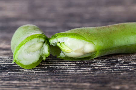 Green pods of ripened beans with green immature moist seeds on a table in a rustic kitchen, close-up 写真素材