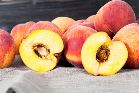 A bunch of peaches of orange color, one peach is cut into two halves and there is a bone in it with traces of putrefaction, although there is no outside damage