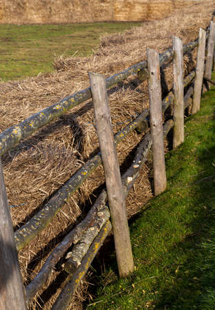 stacks of old last year straw fenced off by a primitive wooden fence