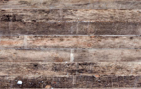 part of an old wooden floor covered with snow and worn out over time, closeup and details of an old wooden gazebo