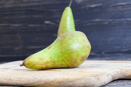 two old green pears lie on an old cutting board made of wood