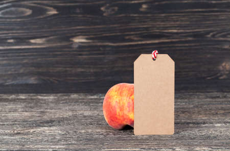 Peaches on a dark background with a label of paper for writing, the label is made from recycled waste paper Stock fotó