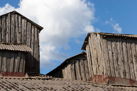 old extensions on the roof of an old building made of boards and logs in the countryside, close-up against a blue sky Stock Photo