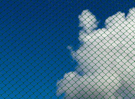 clouds against a blue sky against a metal grid of green, closeup in a fenced area