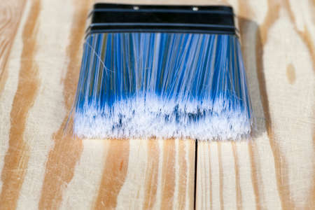 a blue construction brush on the wooden surface of their pine-wood