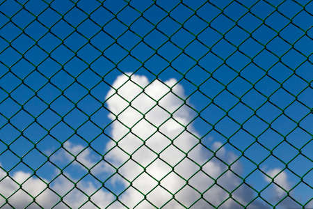 clouds against a blue sky against a metal grid of green, closeup in a fenced area Banque d'images - 111698723