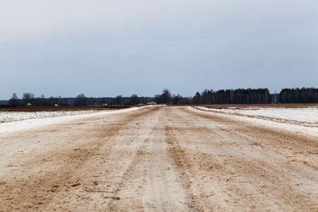 a snow covered road in the winter season, Closeup photo Imagens