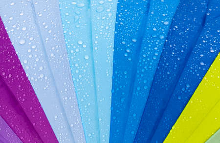 colorful umbrella like a rainbow with drops of water when it rains, closeup in nature