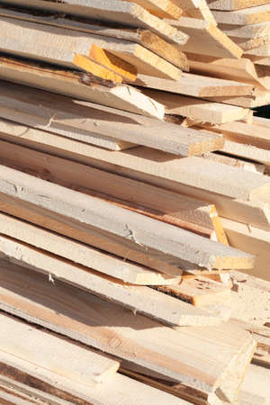 Planed pine boards lying in a heap on a construction site, natural building materials in the production of house, closeup