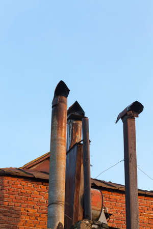 Old thick thin metal chimneys on the roof of a building closeup