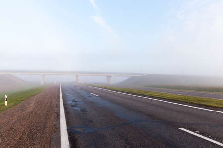 Asphalt road in a big fog, a large road bridge was built across the road Imagens