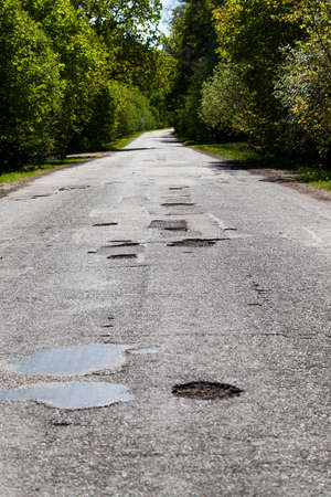 a large number of holes and potholes repaired and patched on the paved road Stock fotó
