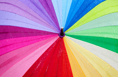 multicolored umbrella covered with drops of water from rain past or walking, closeup useful items, trendy look Stock fotó