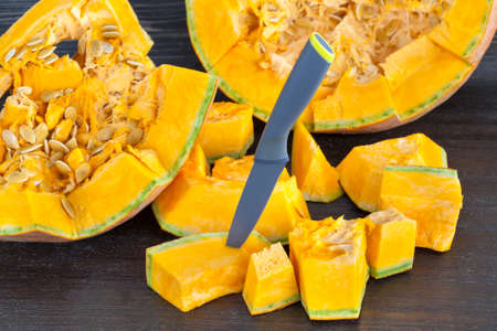 a large pumpkin sliced with a black metal knife while cooking in the kitchen. orange vegetable flesh Stock Photo
