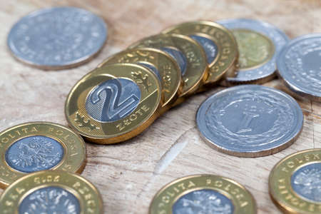 Polish zloty coins lying on an old wooden surface closeup