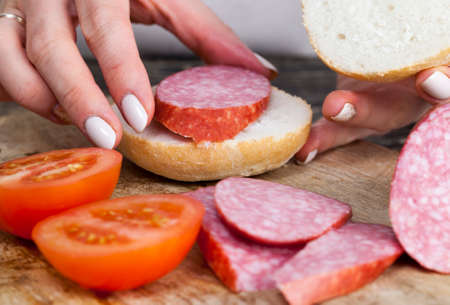 Cooking at home girl sandwich buns from sausage and tomatoes