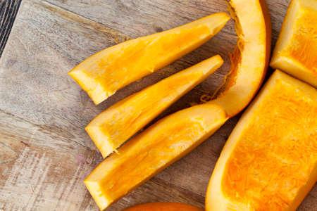 Sliced orange ripe pumpkin while cooking vegetables