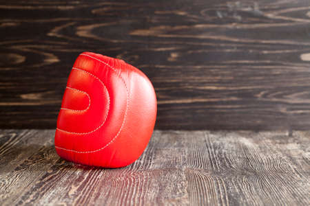 red boxing gloves on black board surface