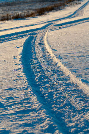 traces of wheels of the car on the snow-covered road. Photographed close-up. On the sidelines of growing grass or cut corn stalks.