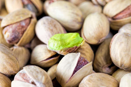 Delicious fried salted pistachios lying in a big heap, close-up edetal some nuts Фото со стока