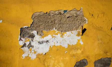 the old brick wall of the house from which part of the plaster has fallen off and destroyed, close-up of an old building during the period of its destruction
