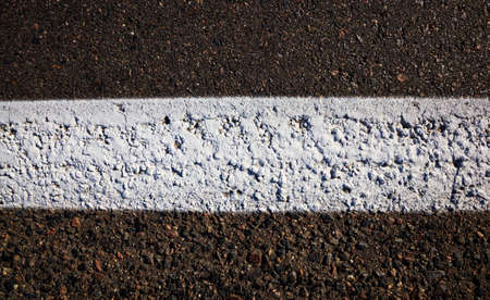 white road markings in the form of a white line drawn on black asphalt to separate car lanes, close-up