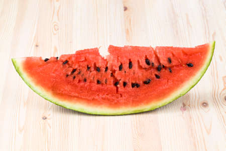 sliced red juicy watermelon with black seeds, close-up of a very tasty berry ripening in late summer or early autumn