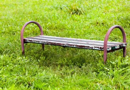 old wooden bench on the background of green grass, close-up in the park in summer or spring