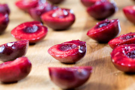 sliced red sweet cherries on a white wooden table, preparing cherries for use in cooking