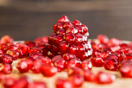 tasty sweet grains of ripe pomegranate on a wooden table, close-up of wholesome berries while breaking a whole fruit