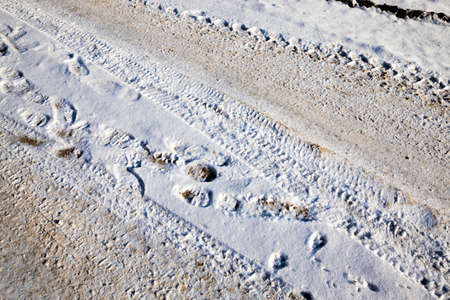 close-up of the road in the winter, traces of mechanical transport in the cold snow after a snowfall, details of the structure and traces of cars,