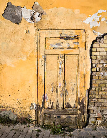 the old brick wall of the house from which part of the plaster has fallen off and destroyed, close-up of an old building during the period of its destruction, closed yellow wooden door