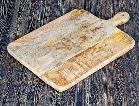old wooden cutting board lying on a dark wooden table, village life Фото со стока