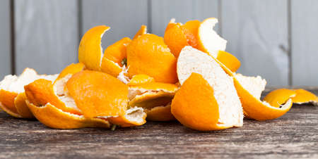 peel from tangerines peeled on a wooden table, orange peel to throw in the trash Фото со стока