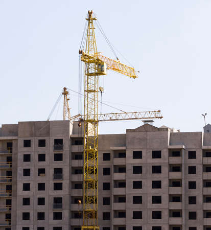 multi-storey house built of concrete blocks and construction cranes standing next to tall cranes made of metal Standard-Bild