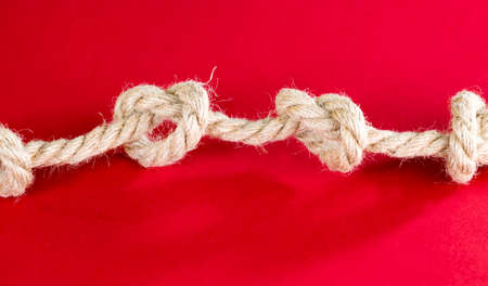 thick linen gray rope tied into knots, details and structure of the rope close-up, used for different purposes Banco de Imagens - 137428645