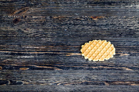 one lying on the wooden surface of wheat sweet waffles, close-up of sweets used as a dessert, top