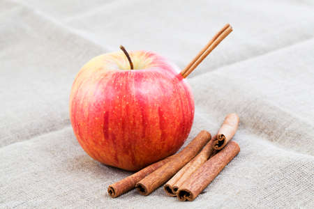 red ripe and juicy Apple with cinnamon sticks, making a delicious dessert of fruits and spices