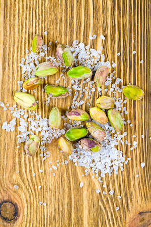 ripe roasted pistachios with salt on a wooden surface