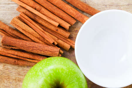 in the peel of a green Apple and fragrant cinnamon on a wooden cutting Board, close-up of food of natural production