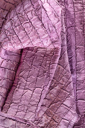 artificial material purple color with irregularly sewn structure, close-up rags pleasant color