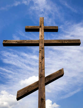 old wooden Orthodox cross against blue sky and white clouds in Sunny weather, close-up of religious symbols