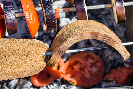 roasted on the fire and burnt coals from logs real shish kebab rye bread, close-up food during outdoor recreation