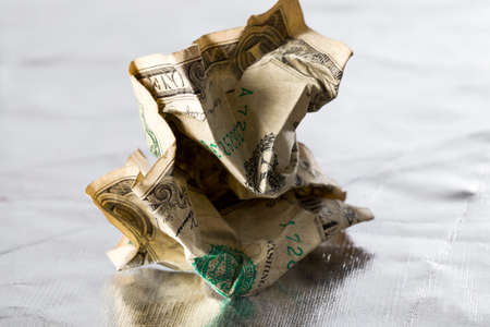 a badly crumpled and battered one American dollar, a close-up of foreign countries money