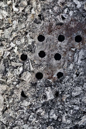 grey cold coals from burnt wooden logs after a fire or bonfire, close-up of ashes in