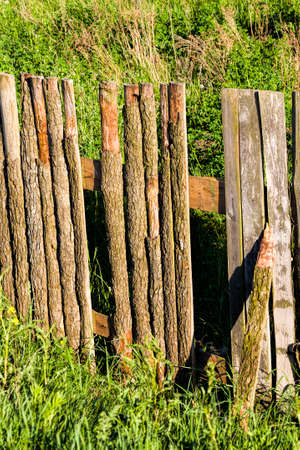 wooden fence made of planks and picket fence, close-up on the territory owned by different people and divided by the old primitive low fence, Eastern Europe