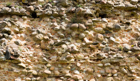 a cracked part of the wall made of stones and cobblestones, a close-up of a piece of poorly made or old construction. Part of the fortress wall