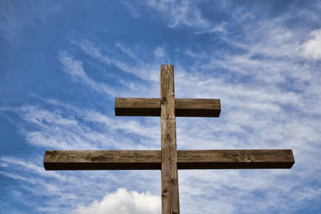 old wooden Orthodox cross against blue sky and white clouds in Sunny weather, closeup of religious symbols