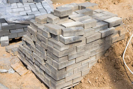 Packed large and long new concrete blocks for curbs and pavers lie on the ground at the construction site PRRI building a new road Stock fotó