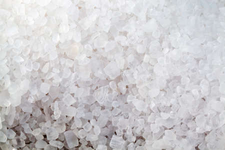large coarse salt on the Board, spices used in cooking, close up and small depth of field